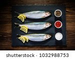 Stock photo fresh raw herrings with herbs served on black stone on wooden table 1032988753