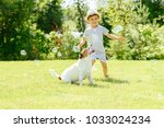 Stock photo happy kid and pet dog playing with soap bubbles at backyard lawn 1033024234