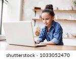 cute little girl using laptop...   Shutterstock . vector #1033052470
