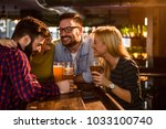 friends in the pub. drinking... | Shutterstock . vector #1033100740