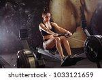 female using rowing machine in...   Shutterstock . vector #1033121659