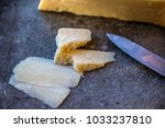 Small photo of Cut and broken pieces of Pecorino Romano cheese on granite tile