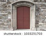 red door in stone wall in... | Shutterstock . vector #1033251703