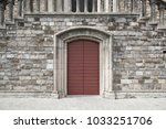 red door in stone wall in... | Shutterstock . vector #1033251706