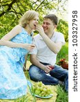 A  man feeding grapes to a picnic man woman - stock photo