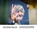 mature woman waiting on window | Shutterstock . vector #1033323490