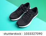 black sneakers on dark green... | Shutterstock . vector #1033327090