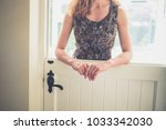 a young woman is standing by a... | Shutterstock . vector #1033342030
