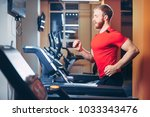 the athlete runs on a treadmill ... | Shutterstock . vector #1033343476