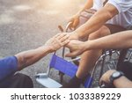 Small photo of Harmonize concept : Three of disabled people sitting on wheelchair and putting their hand together