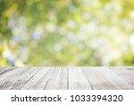 wooden deck with blurred green...   Shutterstock . vector #1033394320