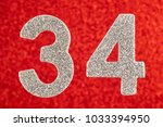Small photo of Number thirty-four silver color over a red background. Anniversary. Horizontal