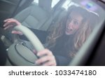 pretty young woman driving her... | Shutterstock . vector #1033474180
