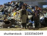 childern at a plactic dump in... | Shutterstock . vector #1033560349
