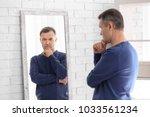 thoughtful mature man standing... | Shutterstock . vector #1033561234