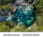 Cenote Azul in the jungle aerial view. People swim in clear water in a cenote that is in the jungle. Top View