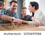 happy family playing board game ... | Shutterstock . vector #1033695586