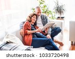senior couple with tablet... | Shutterstock . vector #1033720498
