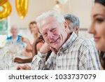 happy senior man at a birthday... | Shutterstock . vector #1033737079