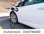 electric car charging on... | Shutterstock . vector #1033786000