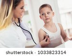 doctor examining a little boy... | Shutterstock . vector #1033823314