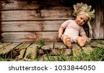 old doll sitting against... | Shutterstock . vector #1033844050