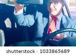 elegant driver looking at rear... | Shutterstock . vector #1033865689