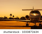 Small photo of Luxury private jet is parked on an airfield during gorgeous golden sunset