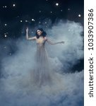 Small photo of An attractive goddess stands in the clouds in a luxurious, gold, sparkling dress. Whimsical hairstyle. Against the backdrop of a star and space. Artistic Photography