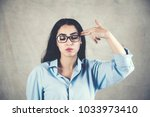 Portrait of a beautiful young girl making gun gesture to her head