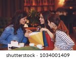 three young women in a cafe... | Shutterstock . vector #1034001409