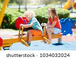 kids climbing and sliding on... | Shutterstock . vector #1034032024