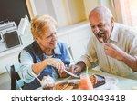 happy seniors couple eating... | Shutterstock . vector #1034043418