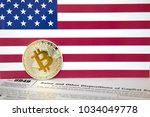 Small photo of Symbolic coin of crypto currency, silver bitcoin with gold B, USA Flag in background, Internal Revenue Service IRS form 8949, concept of an obligation to pay income tax