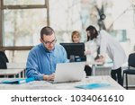 intern at the office working on ... | Shutterstock . vector #1034061610