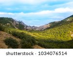 Small photo of Mountain chain covered with trees against blue sky on a sunny day.