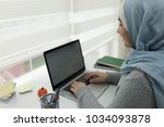 young muslim girl wotking on... | Shutterstock . vector #1034093878