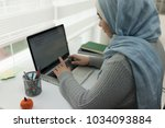 young muslim girl wotking on... | Shutterstock . vector #1034093884