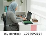 young muslim girl wotking on... | Shutterstock . vector #1034093914