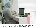 young muslim girl wotking on... | Shutterstock . vector #1034093920