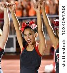 Small photo of Asian American Cheerleader performing at a High School Football Game
