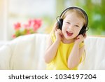 cute little girl wearing huge... | Shutterstock . vector #1034197204