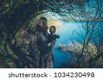 a young mother is standing by a ... | Shutterstock . vector #1034230498