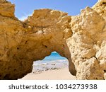 Small photo of Feel like in paradise: A beautiful gate in typical Algarve Cliff at the sandy beach with blue ocean and sky in Portugal