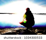 lonely man hiker sits alone on...   Shutterstock . vector #1034300533