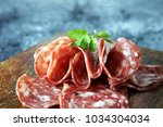 thinly sliced salami on a... | Shutterstock . vector #1034304034