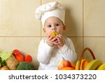 adorable baby boy in kitchen | Shutterstock . vector #1034373220