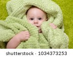 baby boy under the green towel | Shutterstock . vector #1034373253
