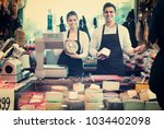 two  happy workers selling... | Shutterstock . vector #1034402098