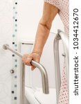 Small photo of Elderly woman holding on handrail in toilet.